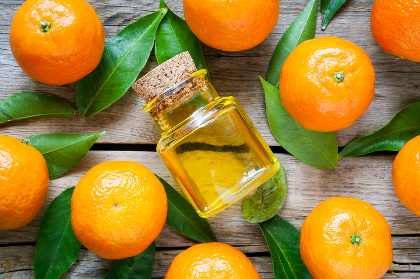 33945440 - ripe tangerines with leaves and bottle of essential citrus oil on a rustic  wooden table. top view.