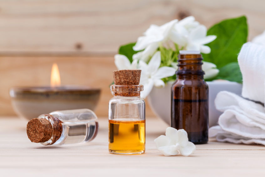 58233680 - bottle of essential oil and jasmin flower with shallow depth of field setup on wooden background .