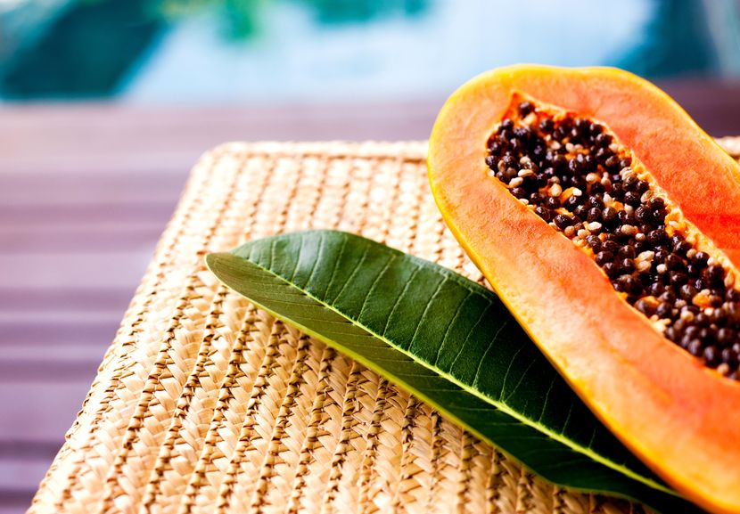 17602198 - juicy papaya and a leaf of a tropical tree on the wicker chair near the swimming pool